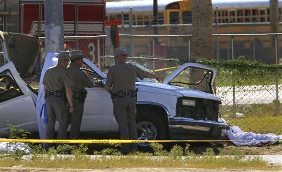 In this Monday, Aug. 12, 2013 photo, Texas Department of Public Safety troopers investigate the scene of a multiple vehicle accident on Western Rd. and Mile 7 northwest of Mission, Texas. Six members of the same family, including two adults and their four children, were killed when an 18-year-old suspect evading troopers in a stolen Ford F250 pickup crashed into their Chevrolet Suburban at high speed. The only survivor was the family's 3-year-old son, according to the DPS. (AP Photo/The Monitor, Nathan Lambrecht) MAGS OUT; TV OUT Photo: Nathan Lambrecht / The Monitor