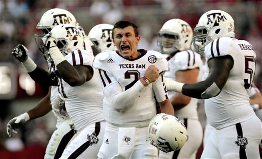"FILE - In this Nov. 10, 2012 file photo, Texas A&M quarterback Johnny Manziel (2) celebrates after a review proves an Aggie touchdown during the first half of an NCAA college football game against Alabama in Tuscaloosa, Ala. ESPN says the NCAA is investigating whether Manziel was paid for signing hundreds of autographs in January. Citing unidentified sources, ESPN's ""Outside the Lines"" said the Heisman Trophy winner signed items in exchange for a five-figure fee during his trip to Miami for the BCS championship game. (AP Photo/The Decatur Daily, Gary Cosby Jr., File) Photo: Gary Cosby Jr. / The Decatur Daily"