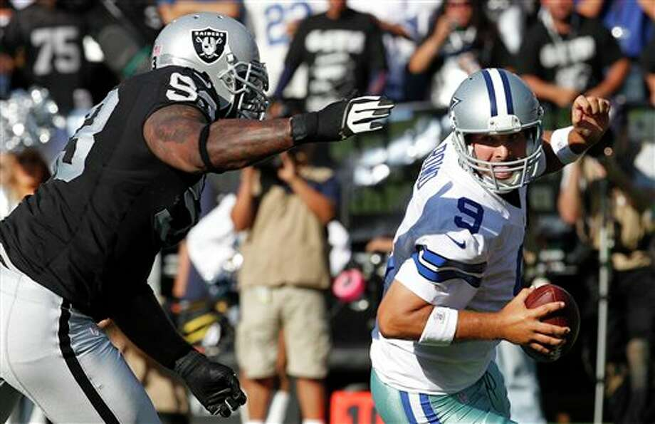 Oakland Raiders defensive tackle Tommy Kelly (93) sacks Dallas Cowboys quarterback Tony Romo (9) during the first quarter of an NFL preseason football game in Oakland, Calif., Monday, Aug. 13, 2012. (AP Photo/Tony Avelar) Photo: Tony Avelar / FR155217 AP