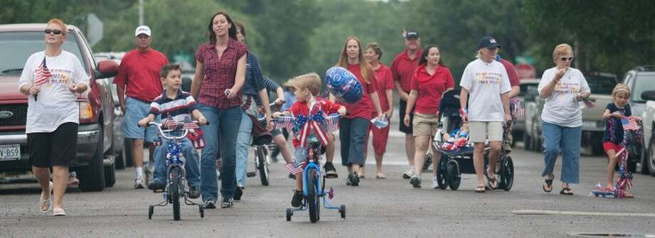 Dozens of parents and their children parade down the 200 Block of South K Street on their decorated bikes, scooters, and wagons during last year's Fourth of July Children's Parade. Photo: Cindeka Nealy