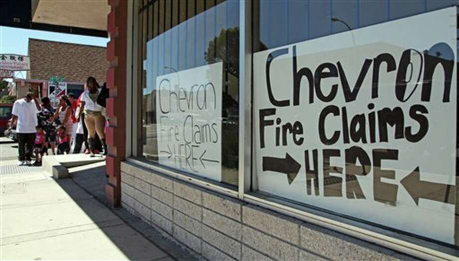 Area residents line up outside the injury attorney offices of R. Nicholas Haney in Richmond, Calif., on Tuesday, Aug. 7, 2012, to pick up a claim form in response to the Chevron refinery fire that impacted the community. Investigators are waiting for access to the charred crude oil unit of a Chevron refinery where a fire sent a towering plume of black smoke into San Francisco Bay area skies and pushed gas prices higher along the West Coast. Hundreds of people went to hospitals with respiratory issues during the fire at the Richmond refinery that produces 16 percent of the region's daily gasoline supply. (AP Photo/Bay Area News Group, Laura A. Oda) MANDATORY CREDIT Photo: Laura A. Oda / Bay Area News Group
