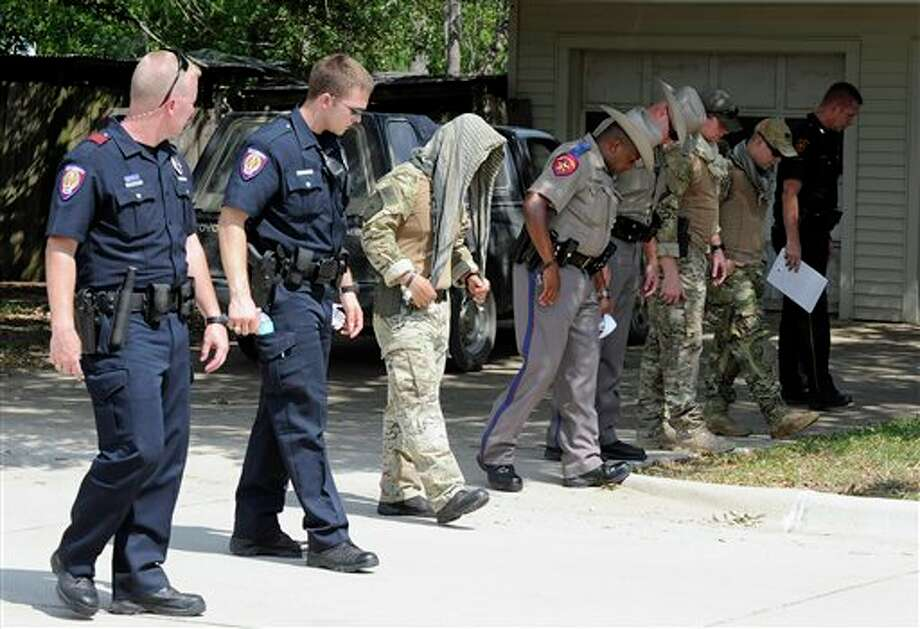 Law enforcement officials conduct a grid search of an area where police say a gunman was being served an eviction notice when he opened fire from inside a home near Texas A&M and killed a law enforcement officer Monday, Aug. 13, 2012, in College Station, Texas. Three people, including the gunman, were killed in the shootout. (AP Photo/Pat Sullivan) Photo: Pat Sullivan / AP2012