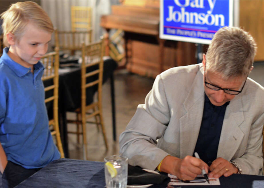 Libertarian Presidential nominee Gary Johnson signs an autograph for 10-year-old Michael Dameron Tuesday at Dee's Bistro & Grill in Odessa. The third-party candidate kicked off his Texas tour in the Permian Basin in an effort to garner more support ahead of the presidential debates. Michael's mother, Charlotte, said it was important for her to teach her son that an individual could make a difference in a grassroots effort. Photo: James Cannon