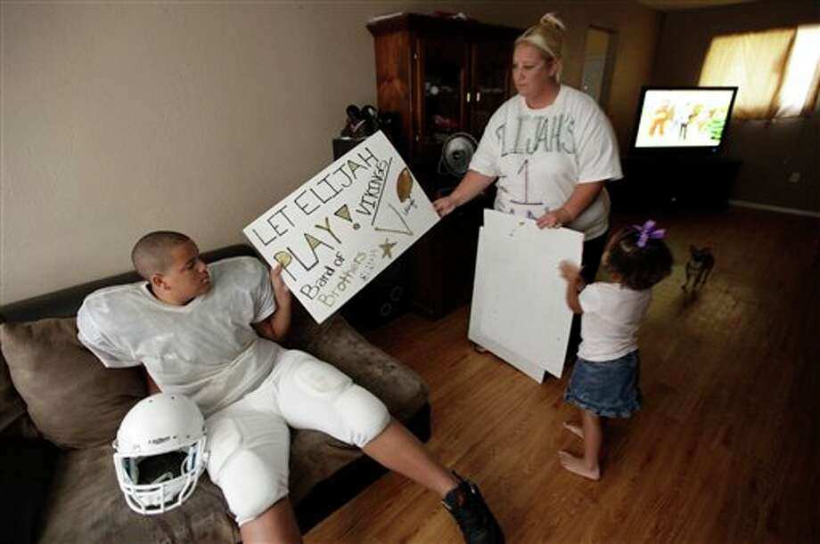 Cindy Earnheart, right, shows a sign she made for her son twelve-year-old Elijah Earnheart, left, as her three year old daughter Larnai tugs at their home in Mesquite, Texas, Thursday, Aug. 16, 2012. The 6-foot, 300-pound 12-year-old has been ruled ineligible to play Pee Wee football in the Dallas area. Despite being a young seventh-grader, officials say is more than twice the maximum allowable Pee Wee weight of 135 pounds. (AP Photo/LM Otero) Photo: LM Otero / AP