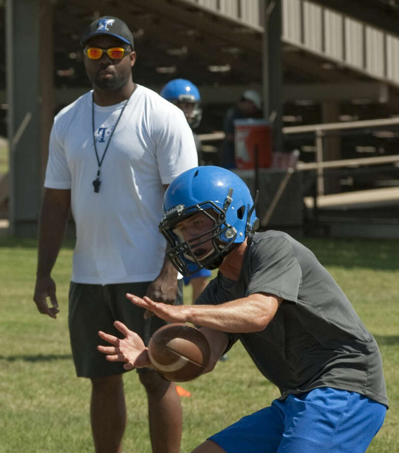 Trinity players run drills Tuesday under the eye of new head coach Antwan Alexander. Tim Fischer\Reporter-Telegram Photo: Tim Fischer