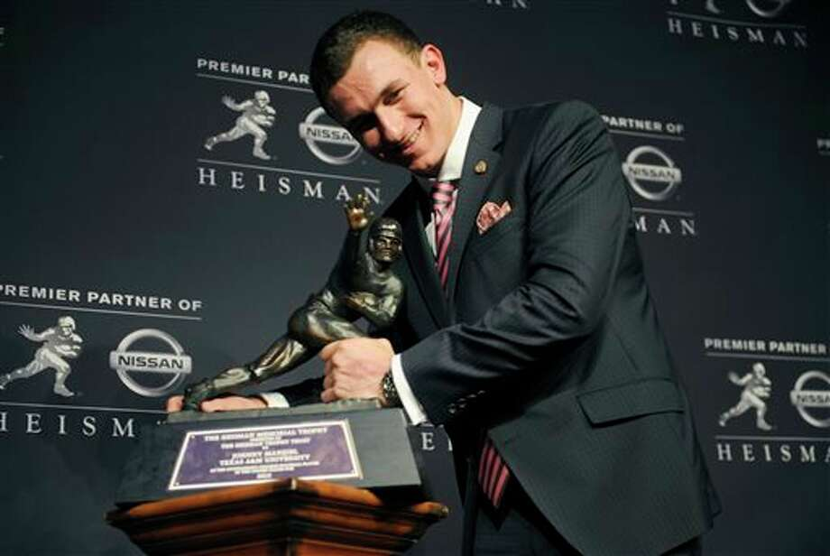 FILE - In this Dec. 8, 2012, file photo, Texas A&M quarterback Johnny Manziel poses with the Heisman Trophy in New York, after becoming the first freshman to win the award. With the NCAA reportedly investigating Manziel for possibly rules violations, could the Heisman Trophy winner be in danger of having the award stripped the way Reggie Bush's was after his NCAA troubles? (AP Photo/Henny Ray Abrams, File) Photo: Henny Ray Abrams / FR151332 AP