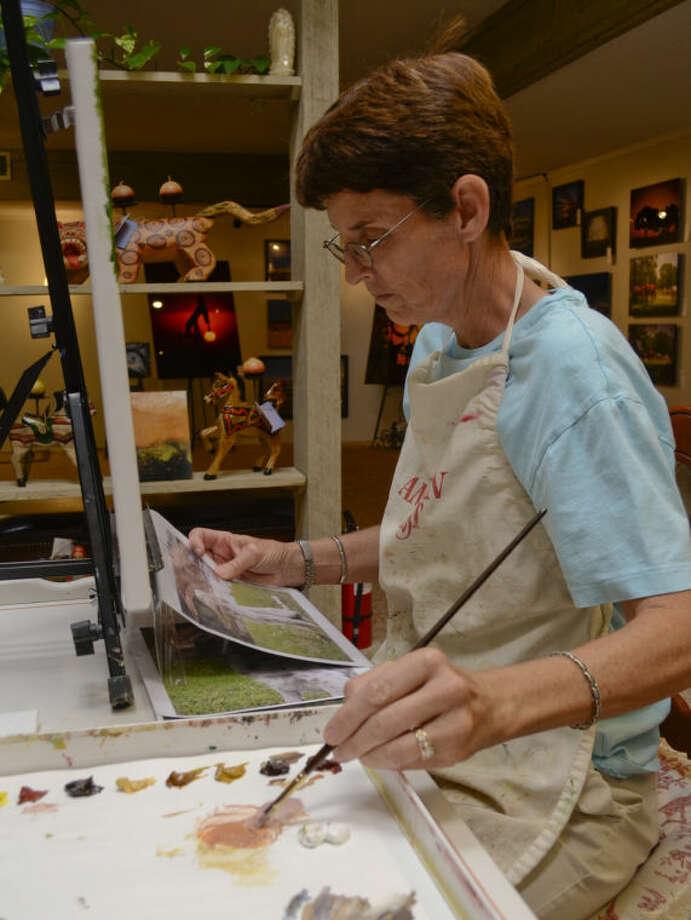 Cheryl Roush works on a painting Tuesday in an area setup inside Artizen Gallery. Tim Fischer\Reporter-Telegram Photo: Tim Fischer
