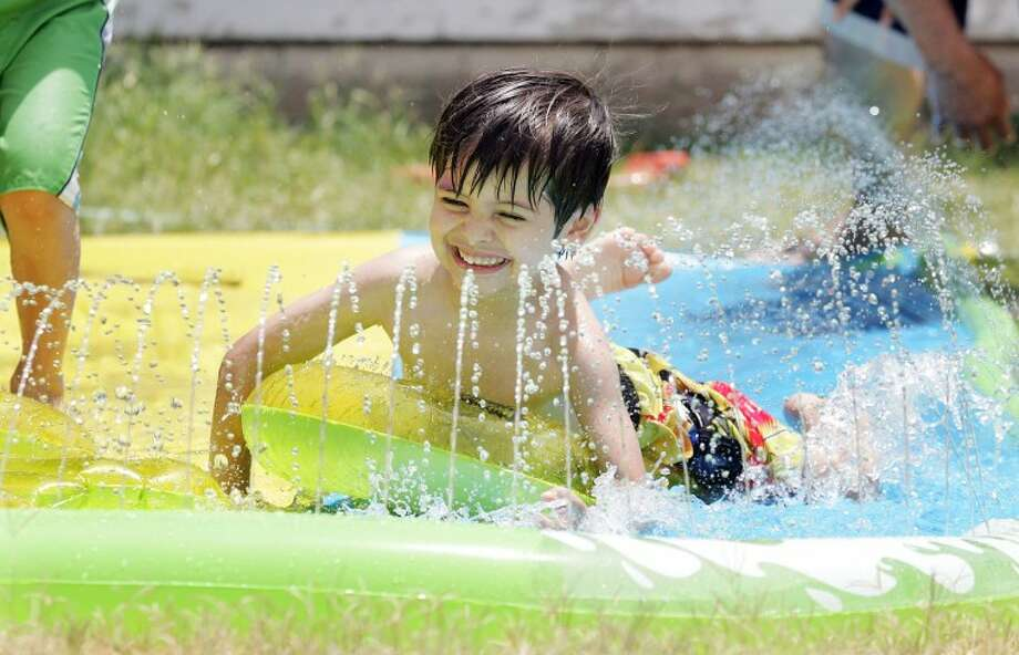 "Maddox De La Pena, 3, finds relief from the warm temperatures as enjoys the afternoon playing with his cousins on the ""Slip N' Slide."" Cindeka Nealy/Reporter-Telegram Photo: Cindeka Nealy"