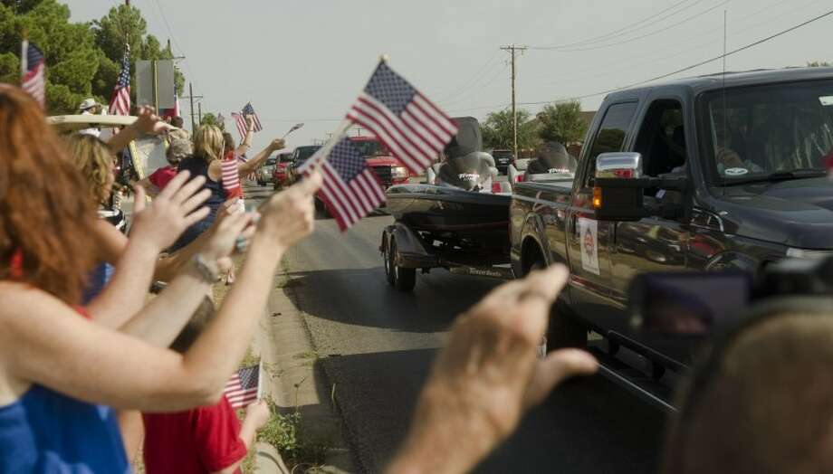 Supporters wave flags and wave to a group of Military men as they pass by Friday morning on their way to a all expenses paid trip fishing on Lake Amistad. Photo by Tim Fischer\ Reporter-Telegram Photo: Tim Fischer