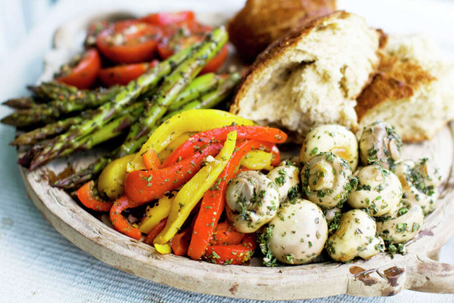 This June 7, 2011 photo shows marinated antipasti vegetables in Concord, N.H. Antipasti doesn't have to be a selection of cheese and fatty cured meats. You can make a delicious and beautiful antipasti platter from the many colors of the vegetable garden. (AP Photo/Matthew Mead) Photo: Matthew Mead / ap