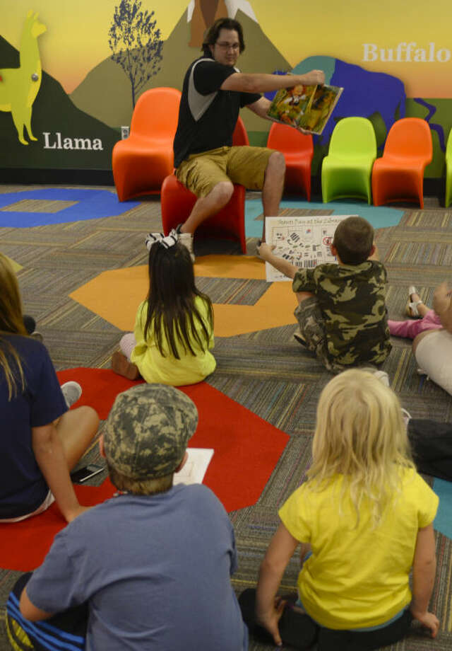 Kelly Brashear, with Midland County Library, reads a story as part of Scouts Day at Centennial Branch Library Monday afternoon. Tim Fischer\Reporter-Telegram Photo: Tim Fischer