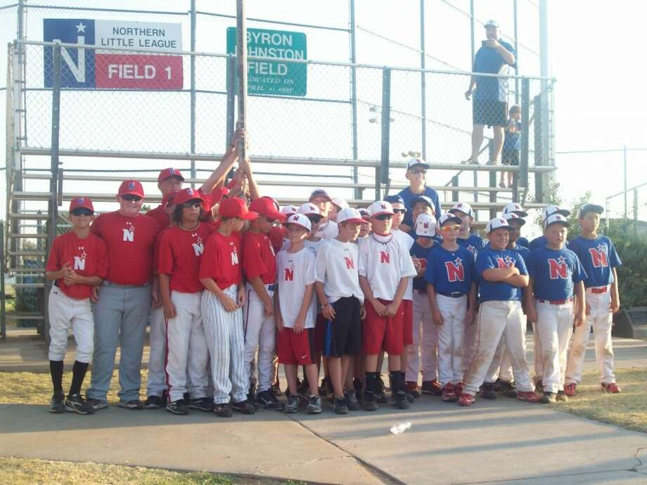 Members of the three Northern Little League teams that won district titles this past week raise the winning flags at Bluebird Park on Wednesday.