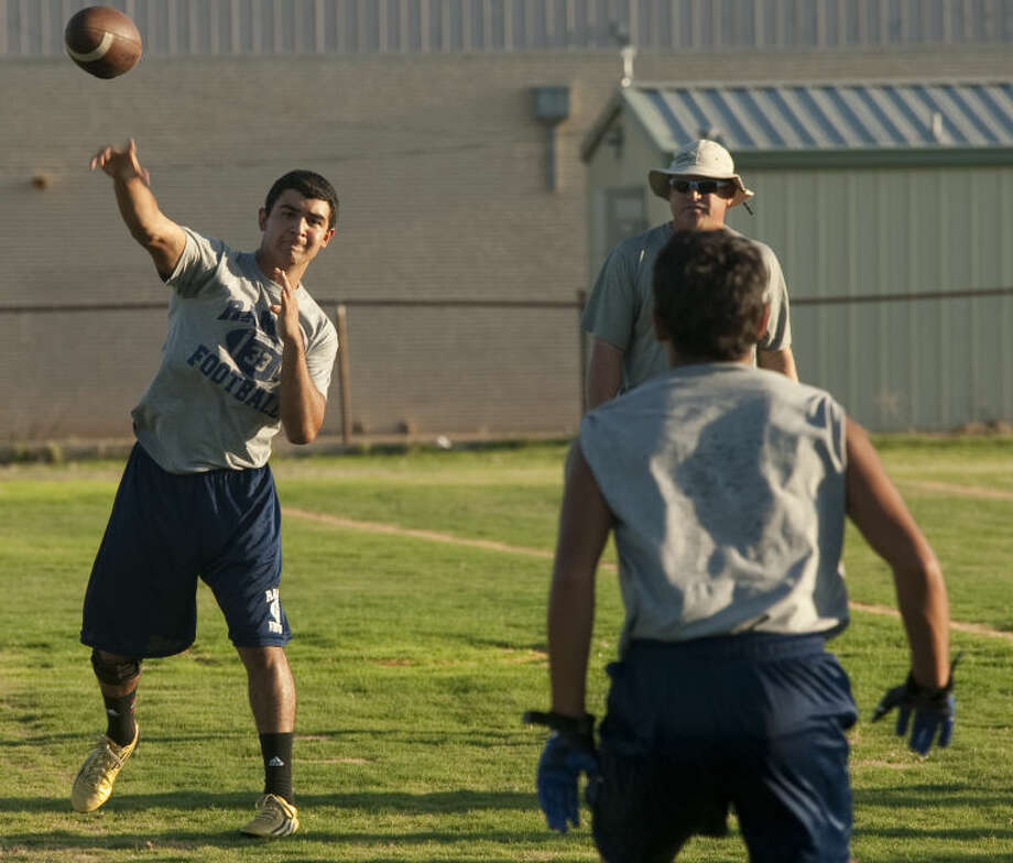 Greenwood QB Anthony Salas practices passes as Coach Shad Hanna watches Monday during the first day of practice. Tim Fischer\Reporter-Telegram Photo: Tim Fischer