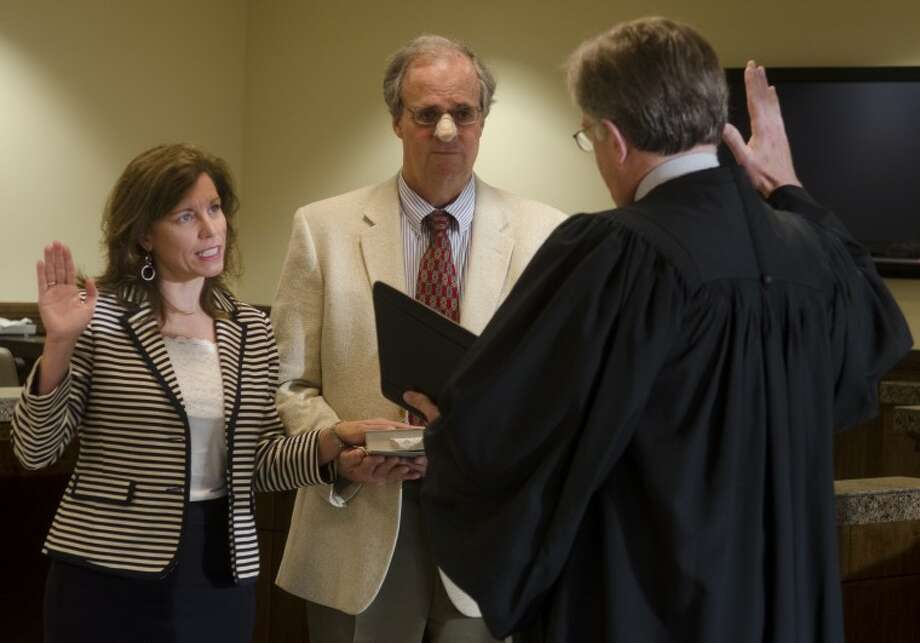 Elizabeth Leonard puts her hand on the Bible as he husband, Dan, holds it for her Monday morning as Judge Dean Rucker swears her in as the 238th District Judge. Photo by Tim Fischer\ Reporter-Telegram Photo: Tim Fischer