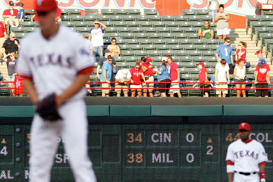 People in the stands react after Texas Rangers fan Shannon Stone fell while trying to grab a ball in the second inning of a baseball game between the Rangers and the Oakland Athletics Thursday, July 7, 2011, in Arlington, Texas. Stone, a 39-year-old firefighter from Brownwood who was at the game with his young son, died at a hospital Thursday night, the Tarrant County Medical Examiner's Office said. (AP Photo/Jeffery Washington) Photo: Jeffery Washington / Jeff Washington Photography
