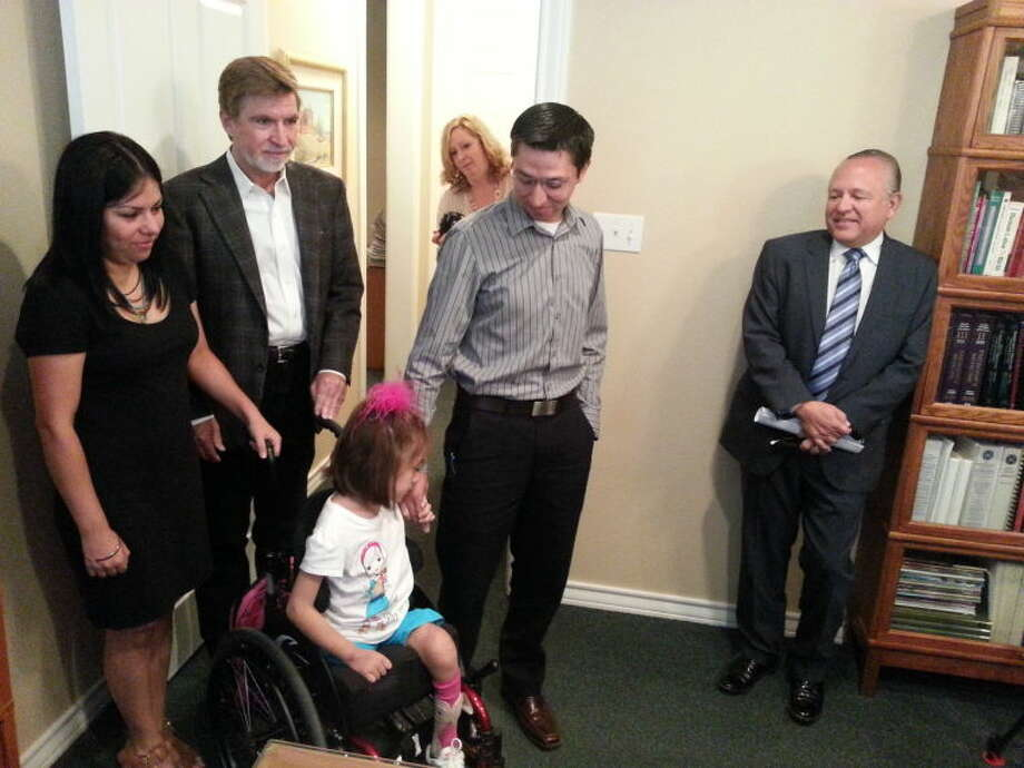 The family of Hannah Hernandez, seated, has filed a malpractice lawsuit against Midland Memorial Hospital and Midland pediatricians. With Hannah at a Monday morning press conference were her parents, Blanca and Victor Hernandez, and attorneys Les Weisbrod, far right, and Kent Buckingham, second from left.