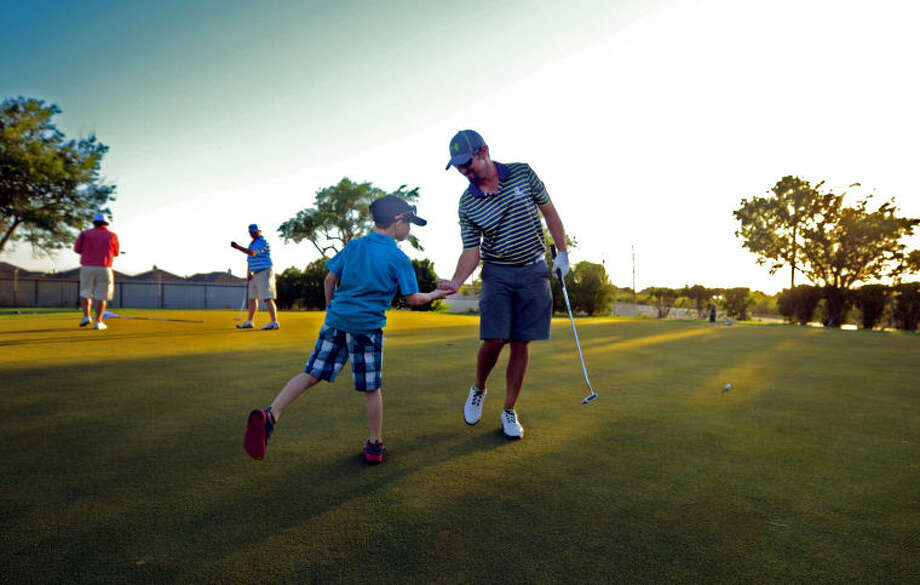 HD Laurence shares is congratulate by his son Patton after sinking a putt on the new green of the 10th hole at Ranchland Hills Golf Club Thursday. The Club recently replaced all of the putting greens on the course. James Durbin/Reporter-Telegram Photo: JAMES DURBIN