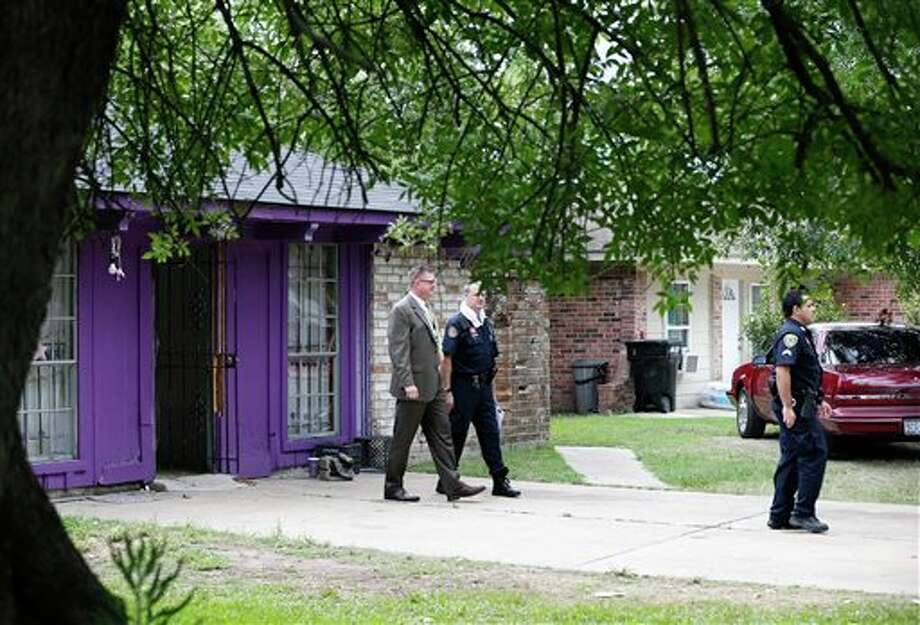 Authorities investigate a home Friday, July 19, 2013, in Houston where police say four homeless men were found in deplorable conditions. Officers who responded to a call expressing concern said said they found three men locked in a garage and a fourth in the home who were malnourished and may have been being held so a captor could cash checks the men were receiving. One person was taken into custody. (AP Photo/Pat Sullivan) Photo: Pat Sullivan / AP