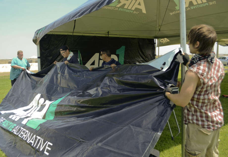 Marshall Stewart, left, Nate Giarratano, Raul Flores and Nathan Madden, promotions for Air 1 radio, set of the Air 1 and K-Love tent Wednesday afternoon as they and others prepare for Rock the Desert music festival starting today. Tim Fischer\Reporter-Telegram Photo: Tim Fischer