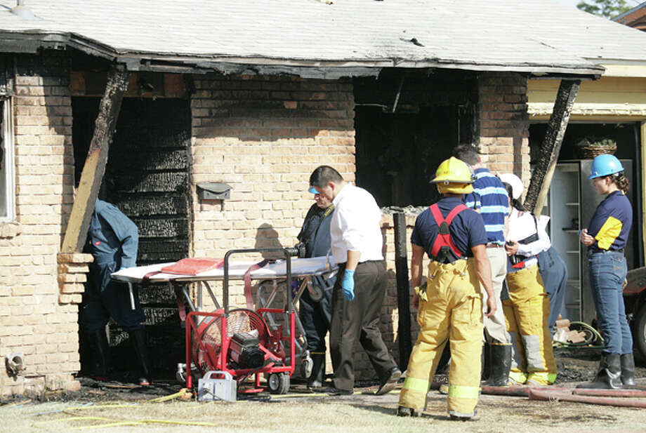 Sanchez Mortician Services personnel walk past Midland police and Fire Department investigators as they enter a residence to retrieve the body of Kay Menefield, 63, who died in a house fire Friday morning on the 3300 Block of Perry Street. Cindeka Nealy/Reporter-Telegram Photo: Cindeka Nealy / Cindeka Nealy/Reporter-Telegram