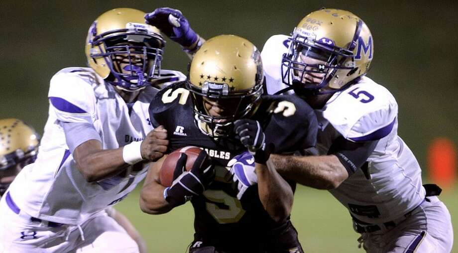 Abilene High running back Paxton Grayer (center) is tackled by Midland High defenders Brandon Williams (left) and Brent Stewart (right) during the fourth quarter of Midland's 30-8 loss on Friday, Oct. 21, 2011, at Shotwell Stadium in Abilene. (Photo by Tommy Metthe/Abilene Reporter-News) Photo: Tommy Metthe