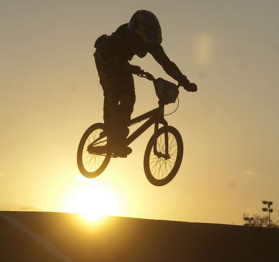 Chrystofer Davis from Midland jumps on of the last obstacles Friday as the sun begins to set as he and others race at the West Texas BMX at Reyes-Mashburn-Nelms Park in Midland. Photo by Tim Fischer/Midland Reporter-Telegram Photo: Tim Fischer