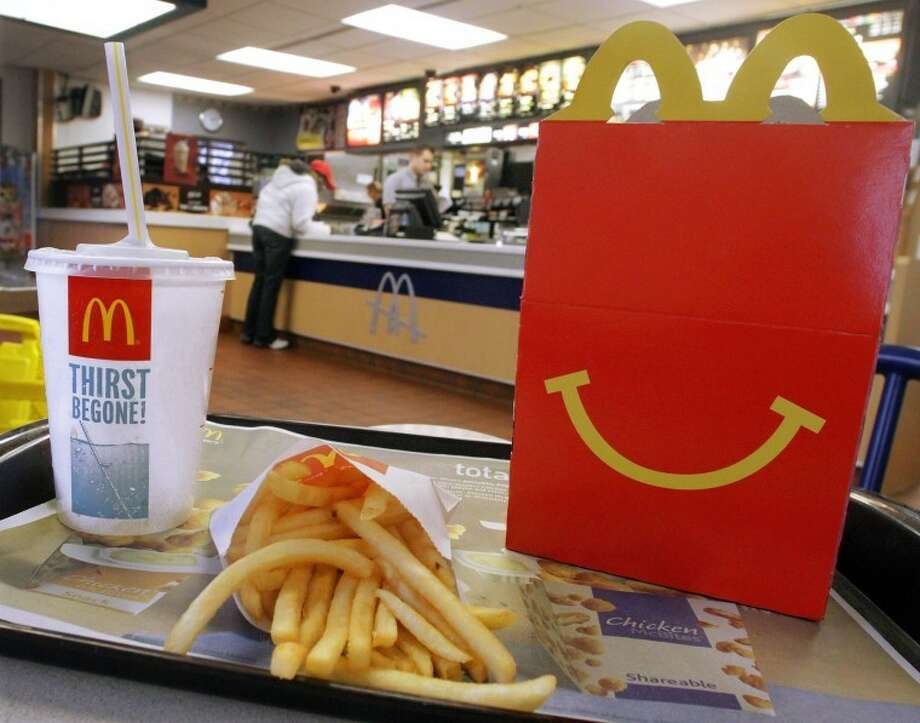 In this Jan. 20, 2012 photo, the McDonald's logo and a Happy Meal box with french fries and a drink are posed at McDonald's, in Springfield, Ill. (AP Photo/Seth Perlman) Photo: Seth Perlman