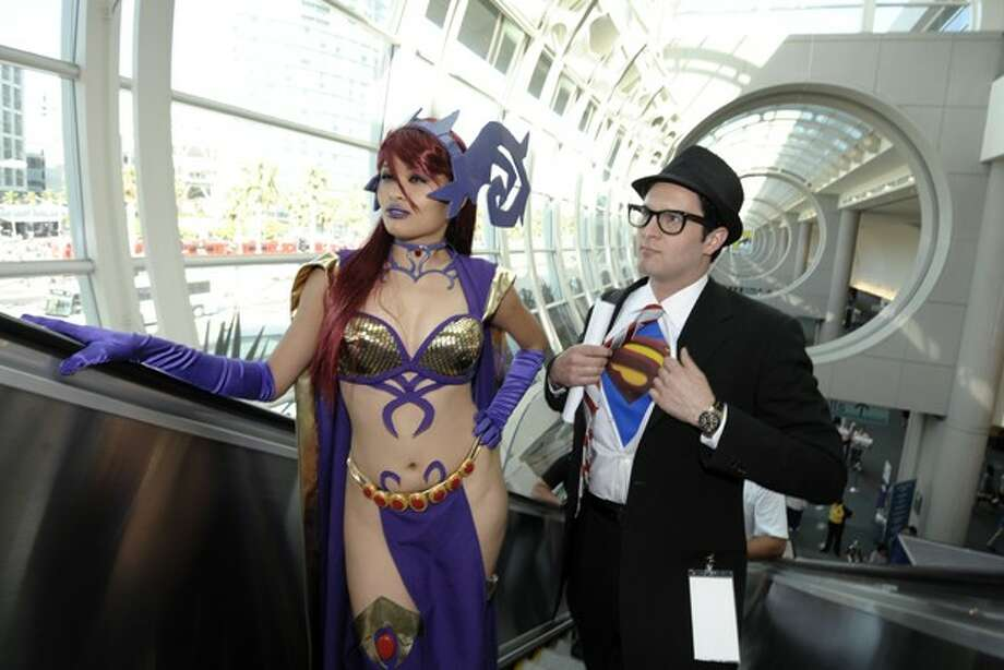 Tracy Ho and Demir Oral pose as they ride the escalator during Preview Night at the Comic-Con 2011 convention Wednesday, July 20, 2011 in San Diego. (AP Photo/Denis Poroy) Photo: DENIS POROY