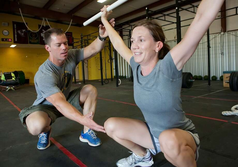 Bryan Ridout works Liz McGehee on her technique during a squat exercise Tuesday at CrossFit Midland. Cindeka Nealy/Reporter-Telegram Photo: Cindeka Nealy