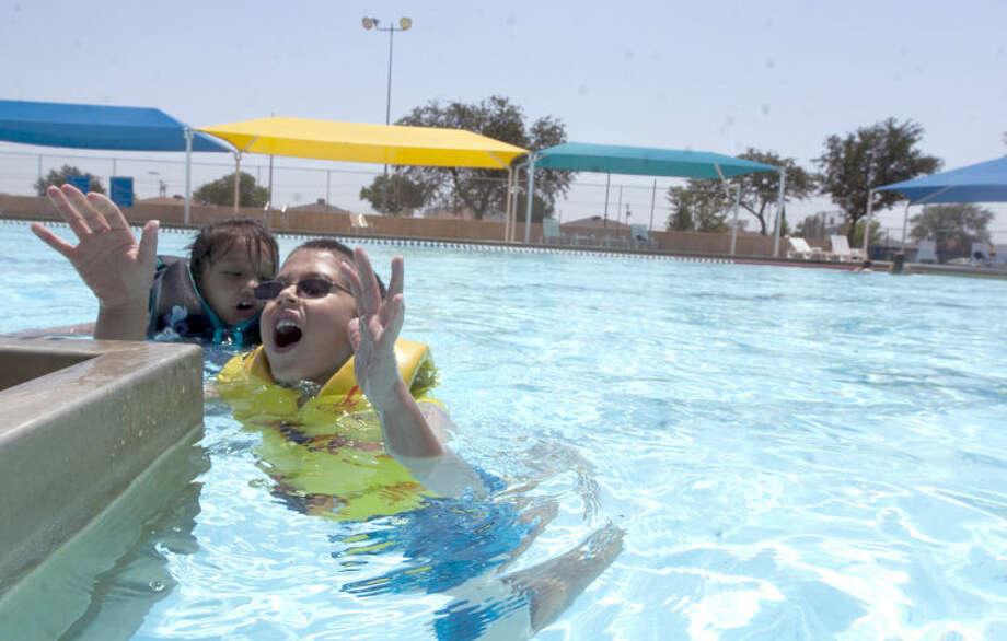 Rylee Hignojos, age 6, and Salvador Amparan, age 6, swim at Doug Russel Pool Saturday. James Durbin/Reporter-Telegram Photo: JAMES DURBIN
