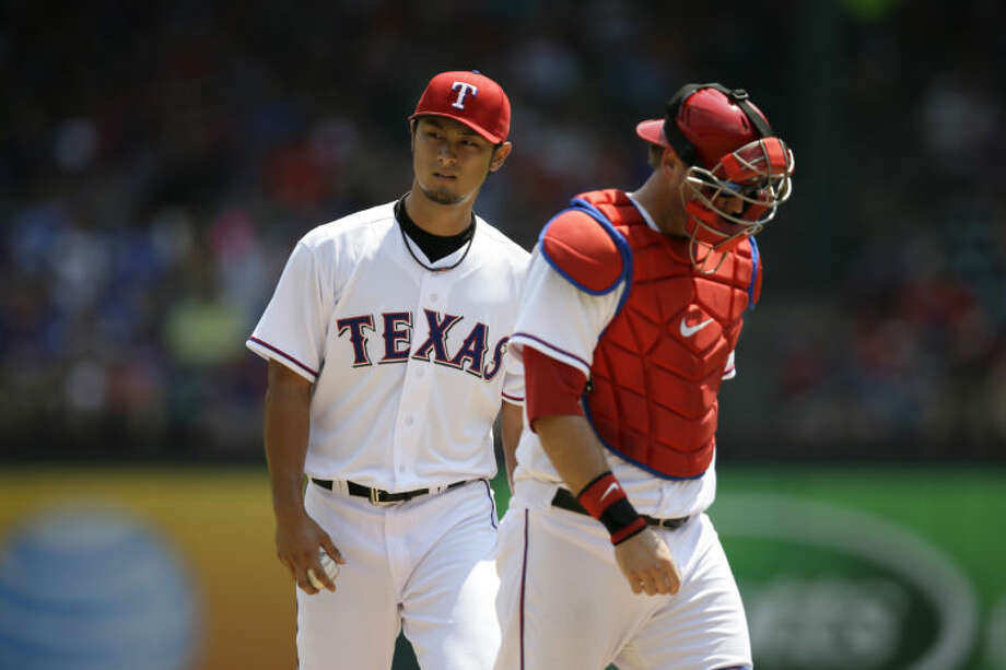 Texas Rangers' Yu Darvish (11) gets a visit on the mound from catcher A.J. Pierzynski, right, against the Seattle Mariners on Sunday in Arlington. (AP Photo/Tony Gutierrez) Photo: Tony Gutierrez