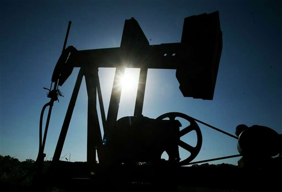 An oil well pumps under the summer sun in a field near Rantoul, Kan., Friday, July 1, 2011. (AP Photo/Orlin Wagner) / AP2011