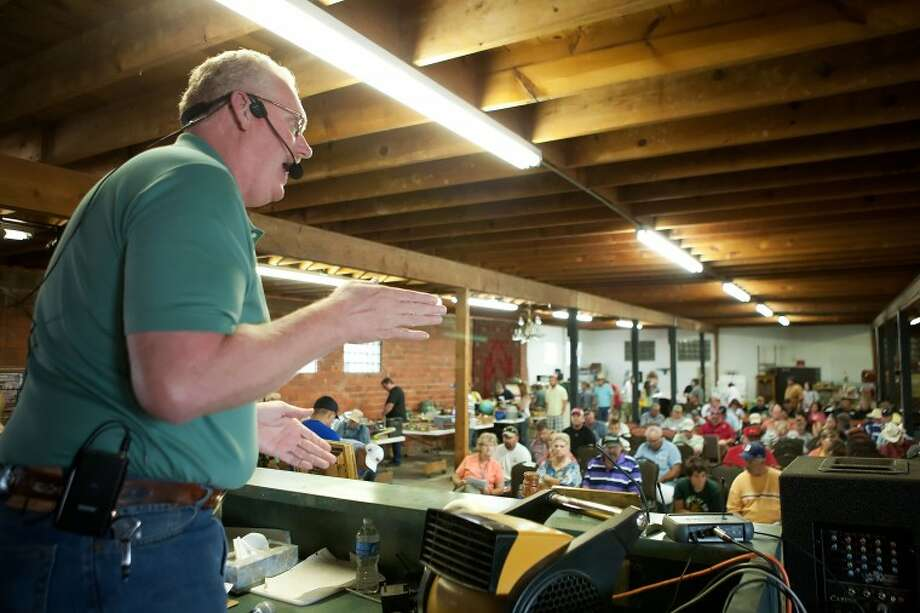 Auctioneer Tim Watkins looks toward the crowd as people bid on items being auctioned off Saturday at Auctions and Services Unlimited. Cindeka Nealy/Reporter-Telegram Photo: Cindeka Nealy