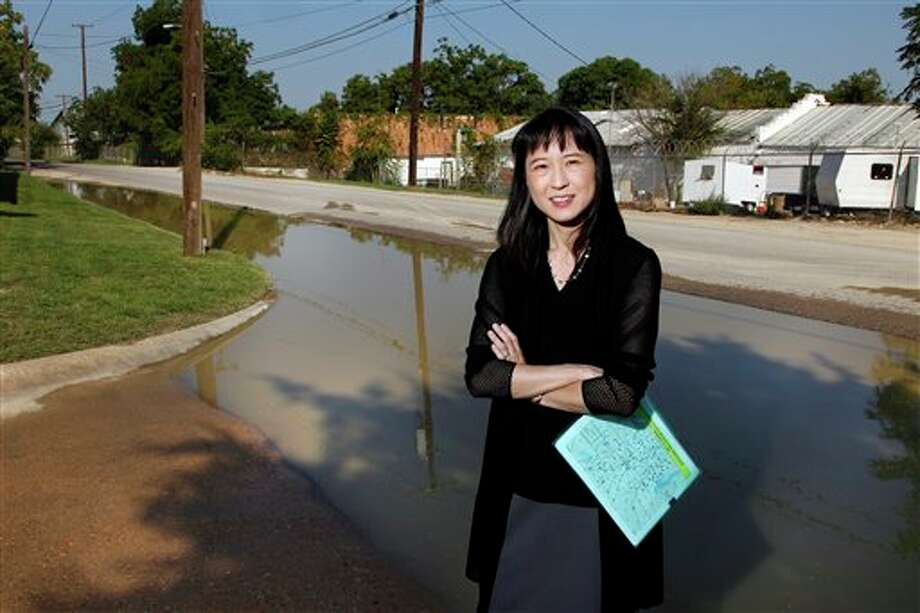 Dr. Wendy Chung, Chief Epidemiologist for the Dallas County Health & Human Services stands in front of standing water, a possible breeding ground for mosquitoes on Aug. 29, 2012 in Dallas. Chung keeps careful watch over the human dimension of the West Nile outbreak. A dozen thick binders stacked on a filing cabinet bear testimony to the epidemic's scope. Each volume is packed with personal descriptions of the illnesses West Nile has unleashed here since June 20, the day the first human infection was confirmed. (AP Photo/The Dallas Morning News, David Woo) MANDATORY CREDIT; MAGS OUT; TV OUT; INTERNET OUT; AP MEMBERS ONLY Photo: David Woo / The Dallas Morning News