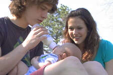 "Emily McKenzie Peterson of Hayden, Alabama, looks on as her boyfriend feeds their baby, Liam, on an episode of the MTV reality series ""16 and Pregnant."""