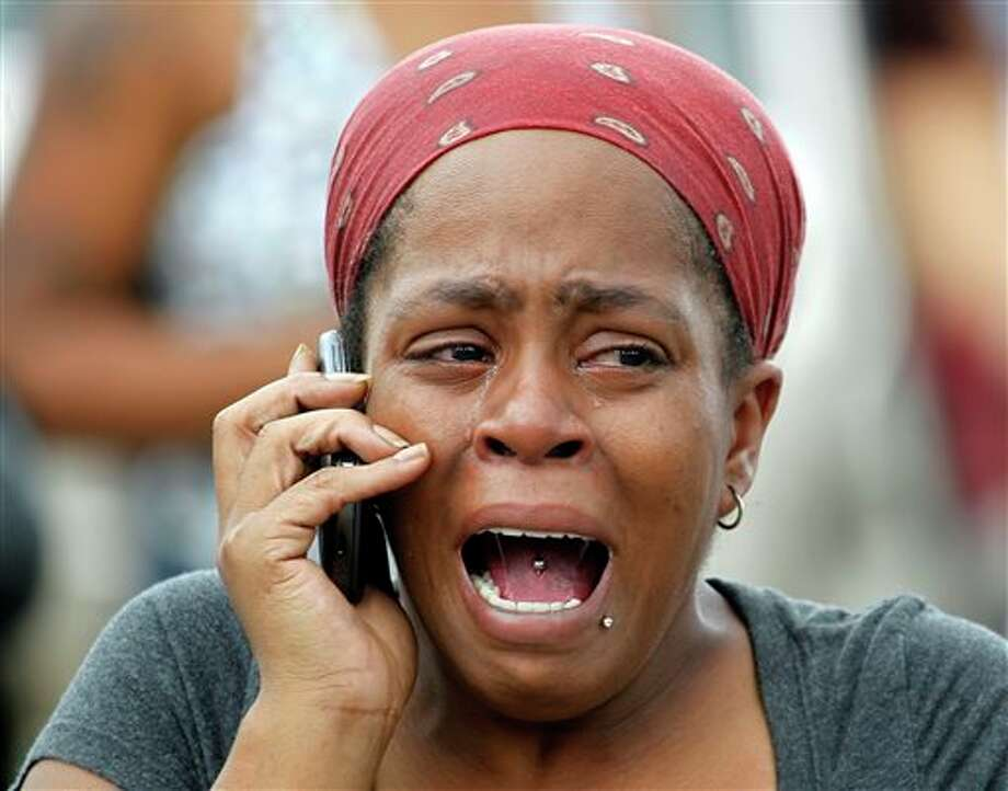 Nicole Webb cries as she talks on a phone in the parking lot of a store while waiting for her 9-year-old son, a student at Ronald E. McNair Discovery Learning Academy in Decatur, Ga., on Tuesday, Aug. 20, 2013. Superintendent Michael Thurmond says all students at the school east of Atlanta are accounted for and safe and that he is not aware of any injuries. (AP Photo/John Bazemore) Photo: John Bazemore / AP2013