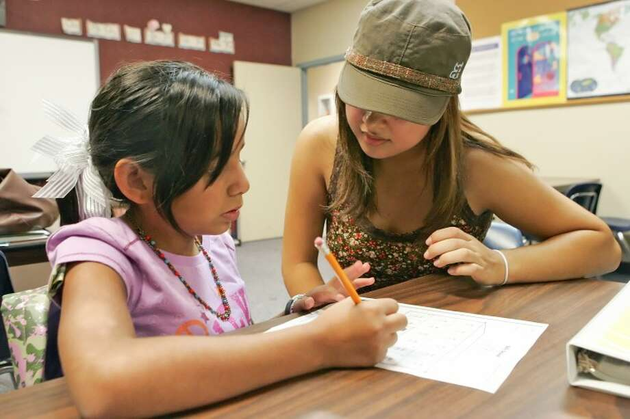 Ylene Madrid, 10, left, gets help with a math assignment from AmeriCorps volunteer Henely Erives, Tuesday at Casa de Amigos. Casa is encouraging parents to bring their children to their free after-school homework help program. Photo: Cindeka Nealy/Reporter-Telegram