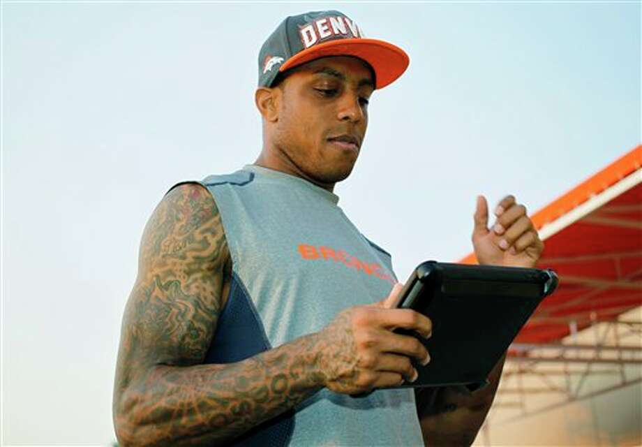 In this photograph taken on Thursday, Aug. 16, 2012, Denver Broncos veteran wide receiver Andre Caldwell looks over the team's playbook on a team-issued computer tablet as he walks off the training field at Broncos' headquarters in Englewood, Colo. Players like the convenience of storing the playbook on computer tablets, which has prompted six NFL teams to retire the traditional printed book in favor of the computer screen. (AP Photo/David Zalubowski) Photo: David Zalubowski / AP