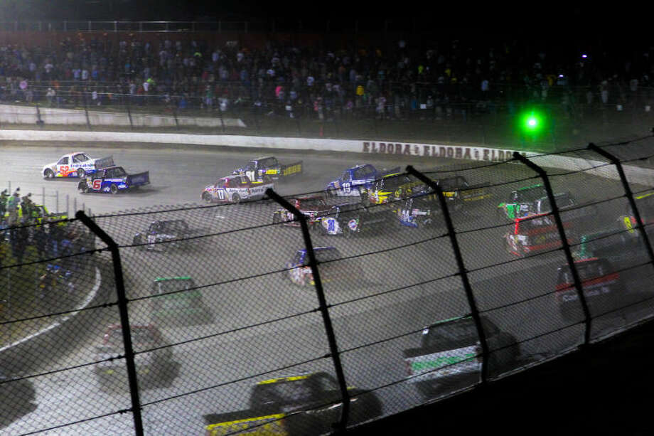 Drivers head through a turn on the opening lap of the NASCAR Truck Series auto race Wednesday, July 24, 2013, on the dirt at Eldora Speedway in Rossburg, Ohio. (AP Photo/Dayton Daily News, Greg Lynch) LOCAL PRINT OUT AND LOCAL TV OUT (WKEF, WRGT, WDTN) Photo: Greg Lynch