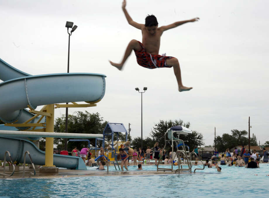 A swimmer jumps off the diving board during Midland County Public Library's end-of-summer swim party. Photo: MARY POWERS