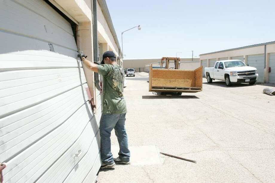 Mark Zumwalt works at repairing one of the 23 storage units that were broken into Tuesday morning at the 2900 W. Kentucky Warehouse Co. Photo: Cindeka Nealy/Reporter-Telegram