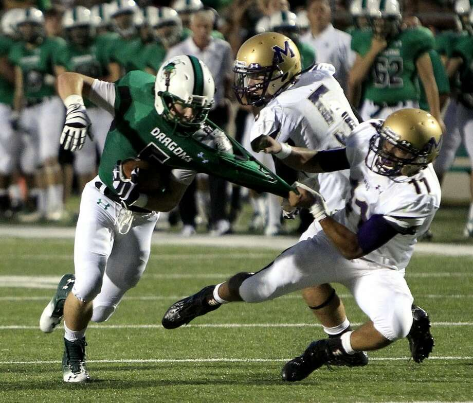 Carroll #5 Ryan Weigel is pulled down by Midland #11 Gilbert Sanchez in high school football Friday September 7, 2012. (Star-Telegram/ Richard W. Rodriguez) Photo: Richard W. Rodriguez