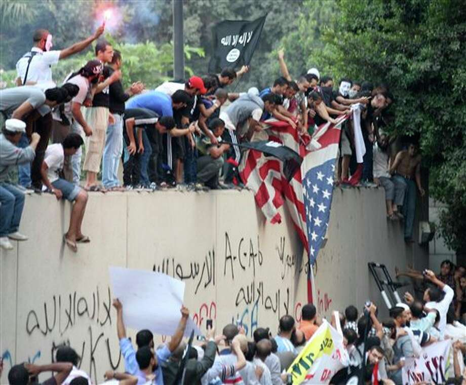 Protesters destroy an American flag pulled down from the U.S. embassy in Cairo, Egypt, Tuesday, Sept. 11, 2012. Egyptian protesters, largely ultra conservative Islamists, have climbed the walls of the U.S. embassy in Cairo, went into the courtyard and brought down the flag, replacing it with a black flag with Islamic inscription, in protest of a film deemed offensive of Islam. (AP Photo/Mohammed Abu Zaid) Photo: Mohammed Abu Zaid / The Associated Press2012