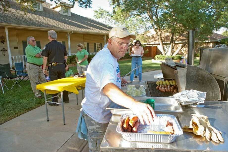Mike Thompson puts food on the grill as his neighbors begin to arrive for their annual National Night Out bloack party Tuesday on the 3600 Block of Woodhaven Court. Photo: Cindeka Nealy/Reporter-Telegram