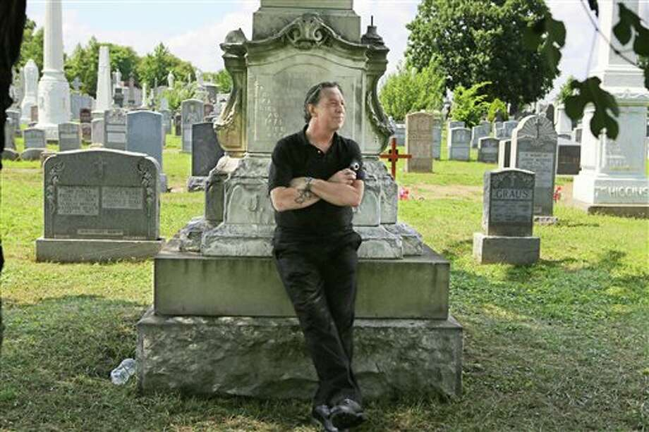 In this Aug. 2, 2013 photo, Patric Abedin, who also goes by the name, Nick Beef, poses for a photo among the grave markers at Calvary Cemetery in the Queens borough of New York. In 1975 Abedin bought the grave plot next to where presidential assassin Lee Harvey Oswald is buried, and then placed the granite marker inscribed with Nick Beef there in 1997. For years, curiosity seekers visiting Oswald's Fort Worth, Texas, grave have wondered about the simple headstone next door. (AP Photo/The New York Times, Nicole Bengiveno) MANDATORY CREDIT; NYC OUT, MAGS OUT; NO SALES; TV OUT; NO ARCHIVE Photo: Nicole Bengiveno / The New York Times