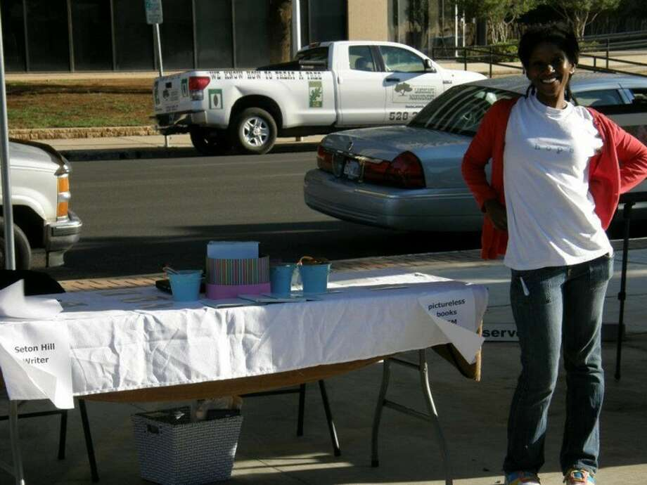 Teffanie White stands beside her booth at last year's Author's Day at the Midland Downtown Farmers Market. Photo: Courtesy Photo