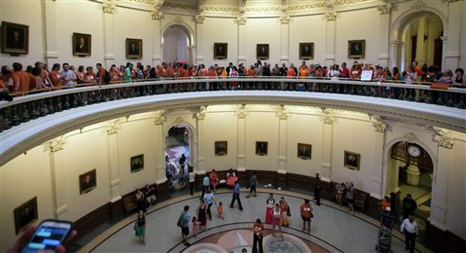 "A large crowd, many wearing Planned Parenthood T-shirts that read ""Stand with Texas Woman,"" wait in line to enter the house chambers at the Texas State Capitol in Austin, Texas on Sunday, June 23, 2013. More than 600 women's rights protesters crowded into the Texas Capitol to watch Democrats begin a series of parliamentary maneuvers to stop the Republican majority from passing some of the toughest abortion restrictions in the country. (AP Photo/Austin American-Statesman/Statesman.com, Ricardo B. Brazziell) Photo: Ricardo B. Brazziell / Statesman.com"