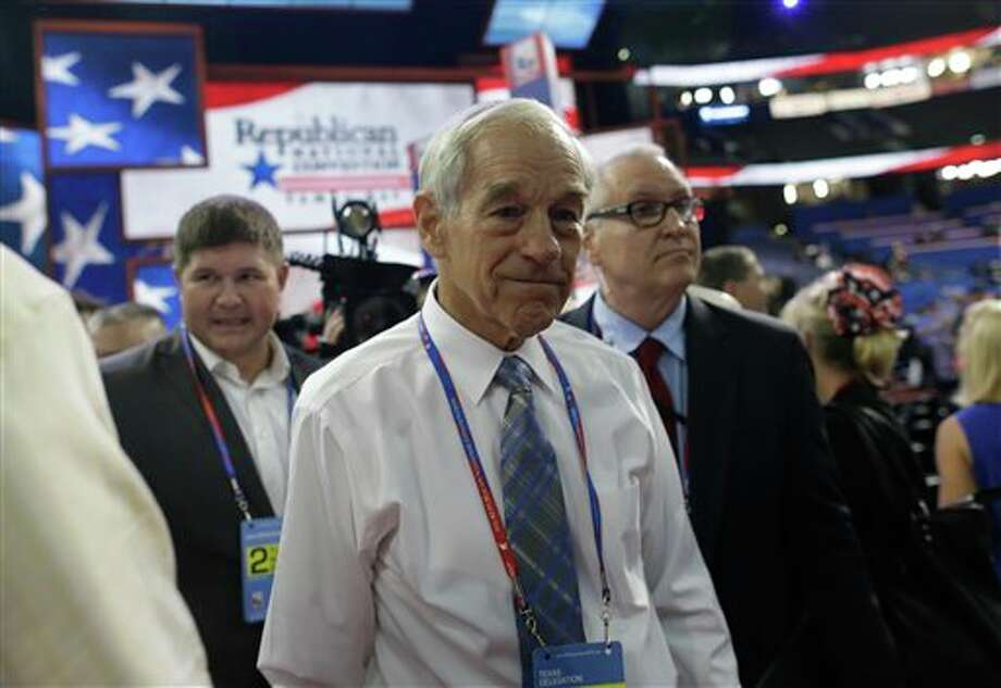 FILE - In this Aug. 28, 2012, file photo, Rep. Ron Paul, R-Texas, arrives on the floor at the Republican National Convention in Tampa, Fla. At least three Republican electors say they may not support their party's presidential ticket when the Electoral College meets in December to formally elect the new president. That prospect is escalating tensions within the GOP and adding a fresh layer of intrigue to the final weeks of the White House race. (AP Photo/Charles Dharapak, File) Photo: Charles Dharapak / AP