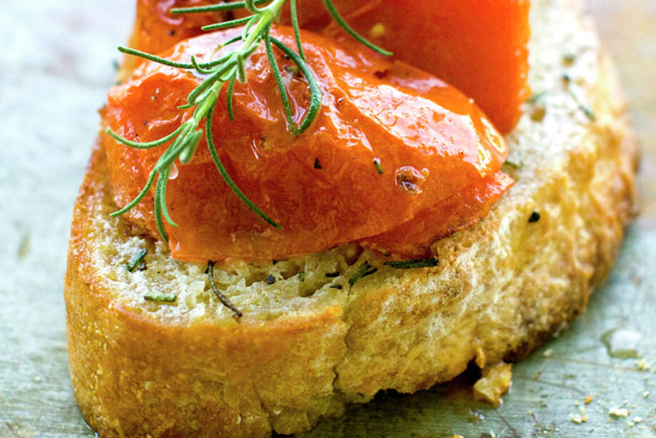 This July 11, 2011 photo shows buttery roasted tomato bruschetta in Concord, N.H. This bruschetta recipe gets a pat of butter added at the end just before serving. (AP Photo/Matthew Mead) Photo: Matthew Mead / ap