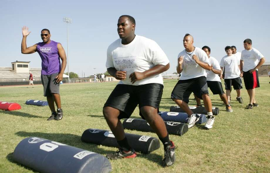 Anthony Alabi, left, coaches Rodrick Jimerson, 17, through offensive line drills Saturday during the Assembly Line Football Camp at Big Spring High School. Cindeka Nealy/Reporter-Telegram Photo: Cindeka Nealy